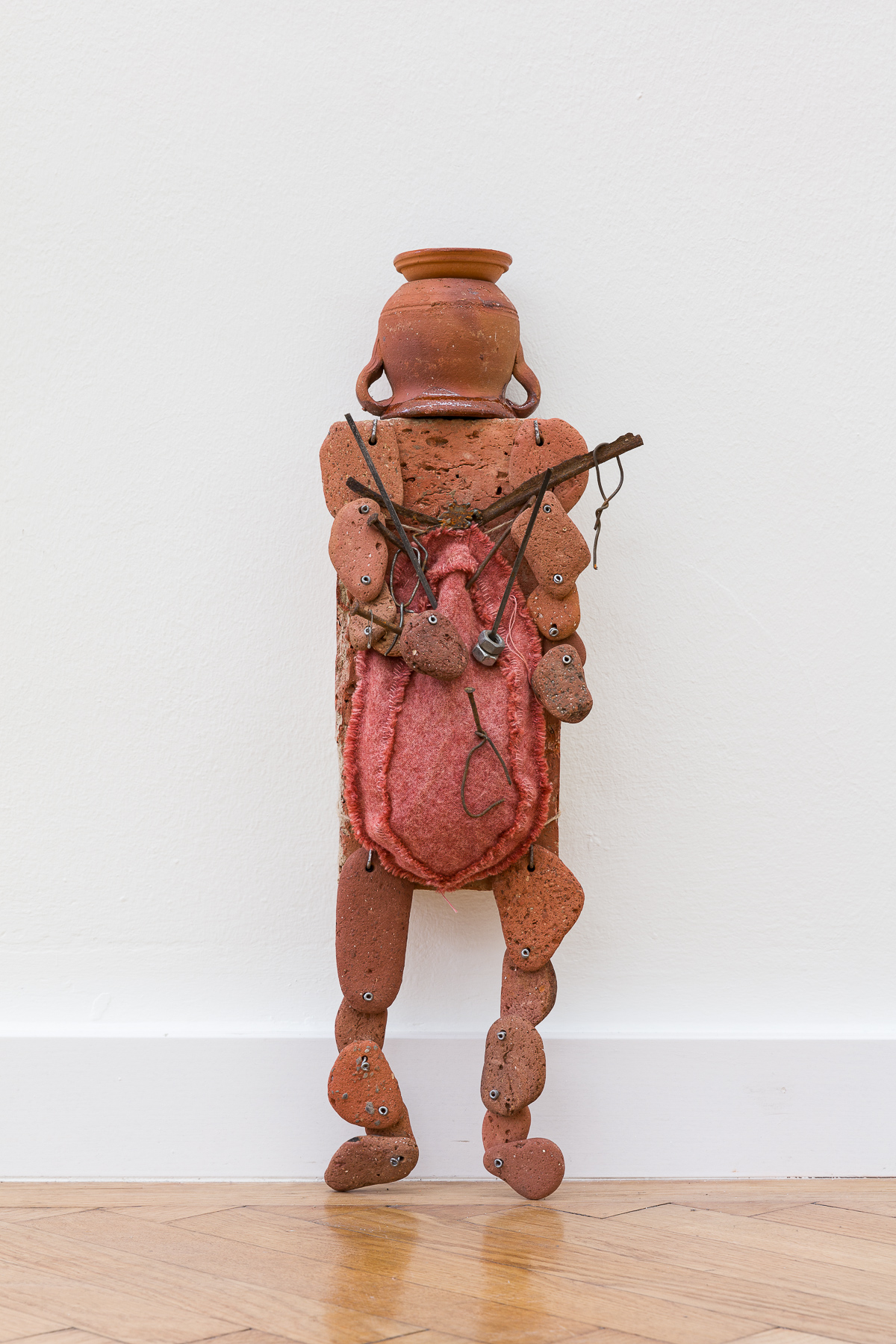 loaf of meat, 2019. Terracotta brick, terracotta pebbles, vessels, fabric, grains of wheat, metal parts. Various sizes.